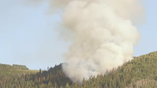 A large mountain wildfire and smoke tilting shot