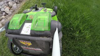 A lawn mower mowing tall grass in the lawn