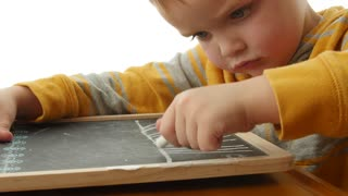 A little boy drawing on a chalkboard