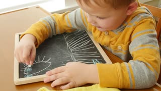 A little boy drawing on his chalkboard in home