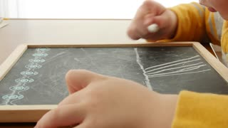 A little boy draws on a chalkboard