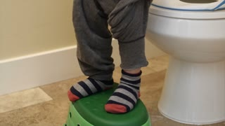 A little boy pulling up pants after going to the bathroom