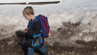 A little boy walks home from school with backpack