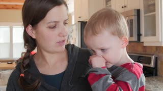 A little toddler blows nose into kleenex