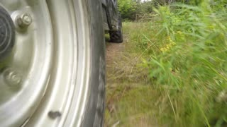 A low shot of a four wheeler side by side tires driving on dirt