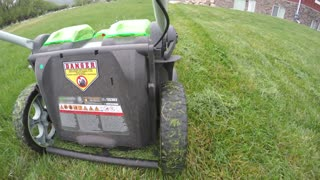A low shot of lawn mower mowing tall grass on the lawn
