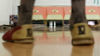 A low shot of people bowling in a small town bowling alley