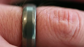a macro of a wedding ring on mans finger