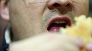 a male eating a hamburger