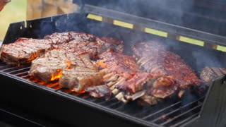 A man barbecues ribs and steak for summer party