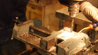 A man drilling through thick metal