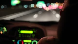 a man driving down highway at night