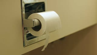 A man grabs toilet paper while using the bathroom in a hotel