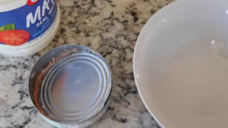 A man opens a can of tuna fish for sandwich
