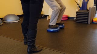 A man practices balance in physical therapy dolly shot