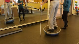 A man practices balance in physical therapy dolly