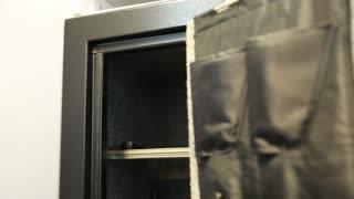 a man puts back a pistol from his gun safe