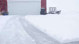 A Man Snowblowing His Driveway During A Blizzard