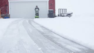 A Man Snowblowing His Driveway During The Blizzard