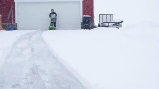 A Man Snowblows His Driveway During A Blizzard