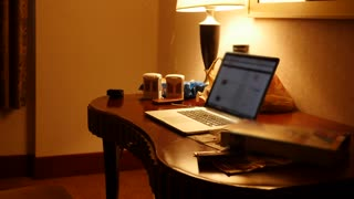 A man working in dark hotel room at night on computer sits down
