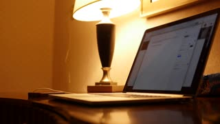 A man works on a laptop in hotel room late at night