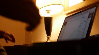 A man works on laptop in hotel room late at night