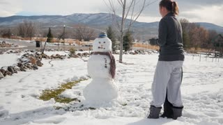 A Mother And Boy Making A Fun Snowman In Their Yard