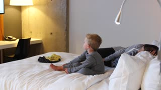 A mother and toddler in hotel room bed