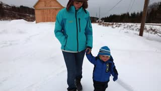 a mother and toddler walking through snowy forest