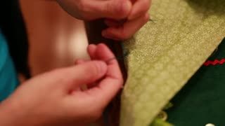 a mother sewing a christmas advent calendar