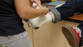 A nurse tapes a boys sprained ankle