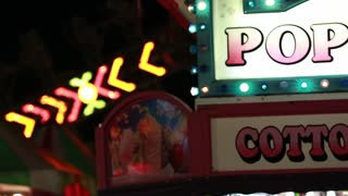 a popcorn and cotton candy sign at carnival