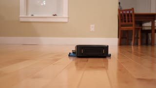 A Robot Mop Cleaning The Floor Inside Home