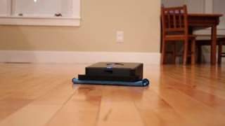 A Robot Mop Cleans The Floor Inside Home