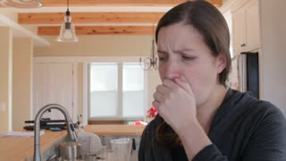 A sick woman blows nose in kleenex