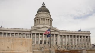A slow Motion Dolly shot of flags at the Utah State Capitol Building