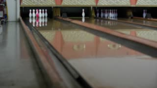 A slow motion shot of a bowling ball getting strike