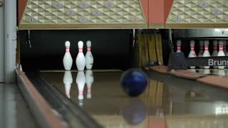 A slow motion shot of ball hitting the bowling pins