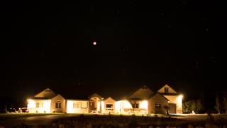 A timelapse of blood moon over large house