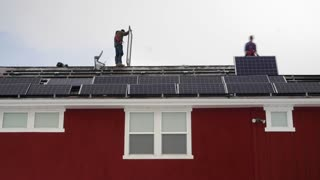A timelapse of crews placing solar panels on the roof of a house