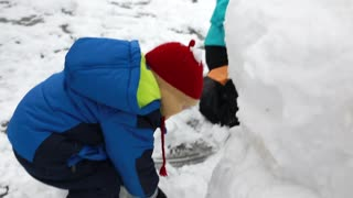a toddler making snowman with his mother