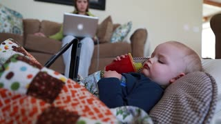 a toddler sick with a flu watching tablet near mother