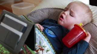 a toddler sick with the flu watchin a tablet