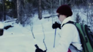 a woman cross country skiing in forrest