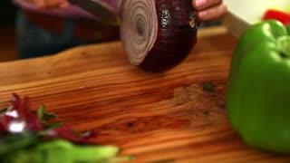 a woman cuts a red onion for a greek salad