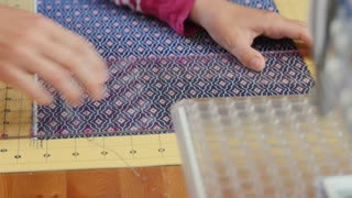A woman cutting fabric to sew