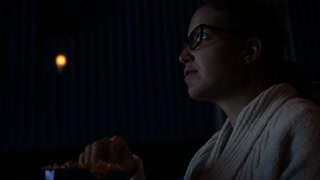 A Woman Eating Popcorn Watching Movie In Theater