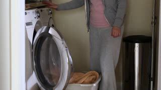 a woman puts dirty clothes into washing machine