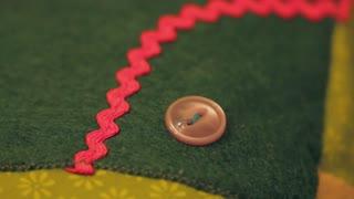 a woman sewing buttons onto advent calendar